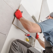 Worker adding tile to bathroom wall